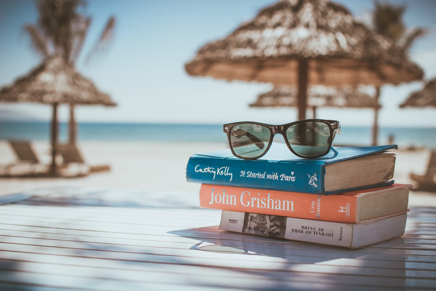 picture of someones summer holiday with books and sunglasses