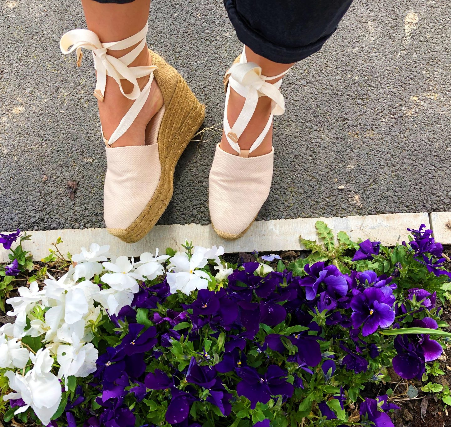 Cream Castañer espadrilles in front of a garden full of pansies