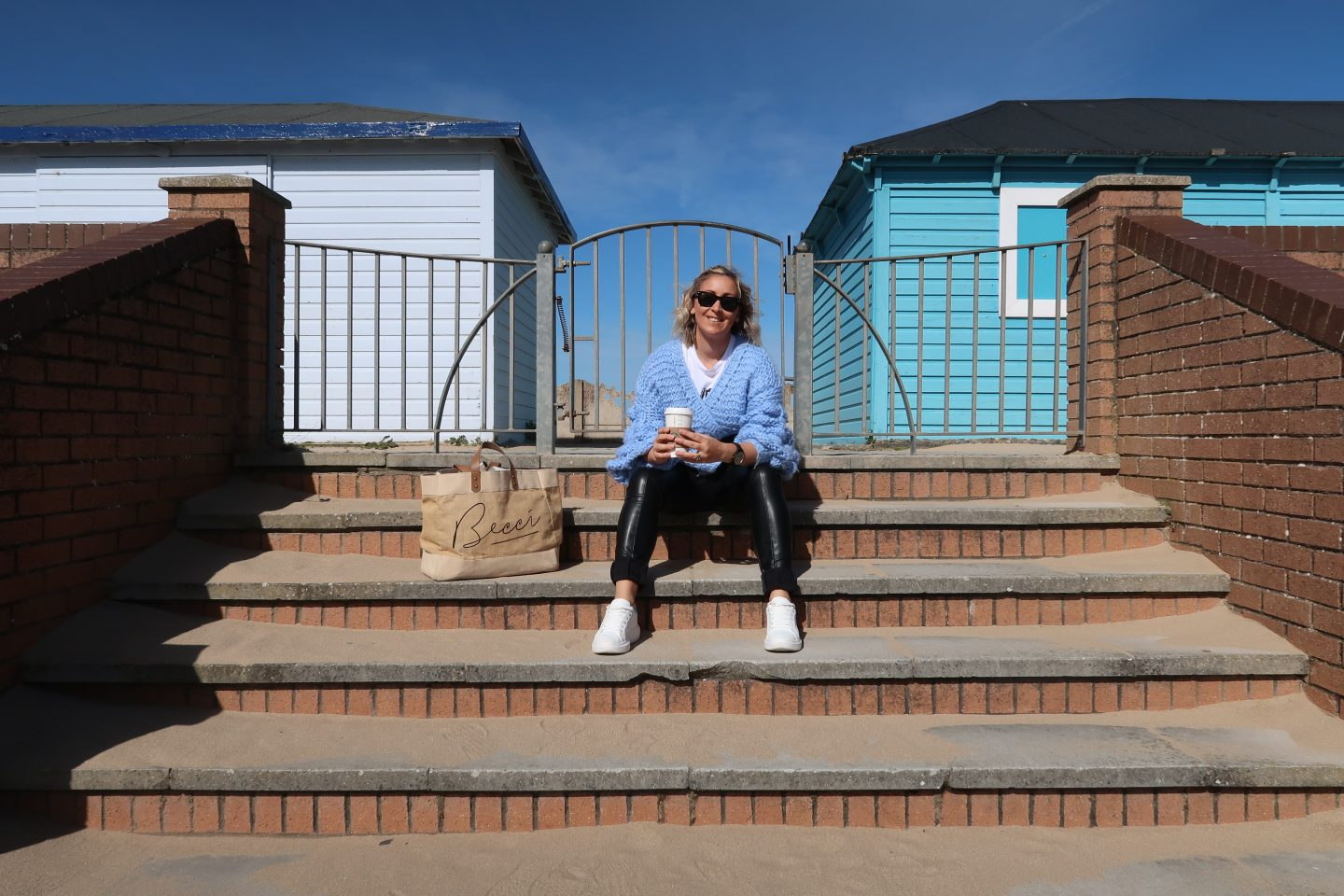 Becci looking very happy sat on a step with a coffee and her bag. Becci is wearing a blue jumper and wearing sunglasses