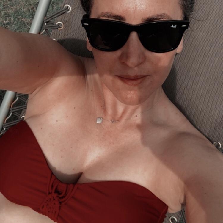 Becci sitting in beach chair wearing Protest bikini
