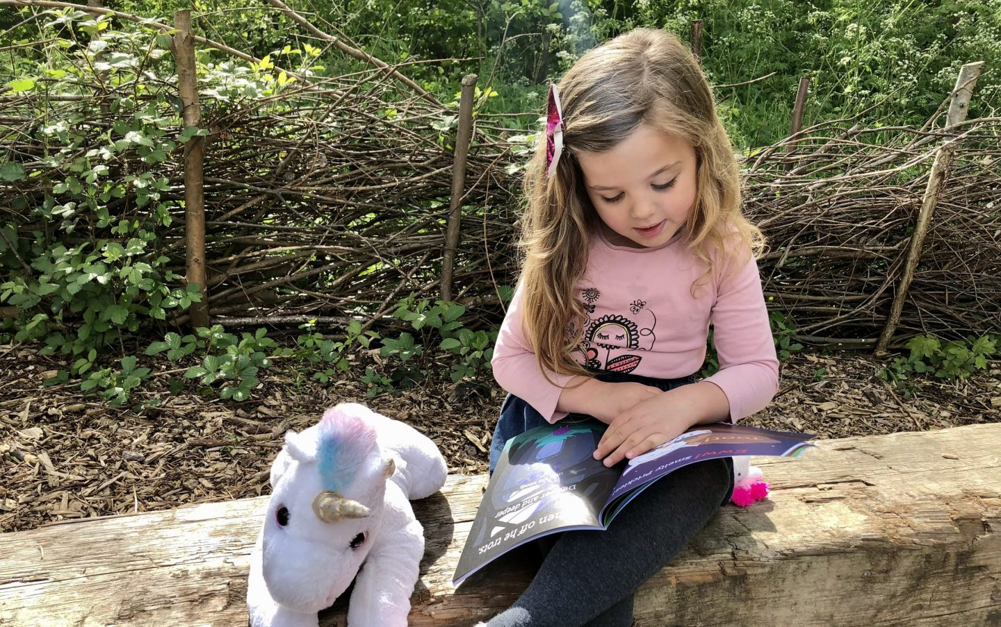 Charley reading Prickles the Hogglypot on a log in the woods