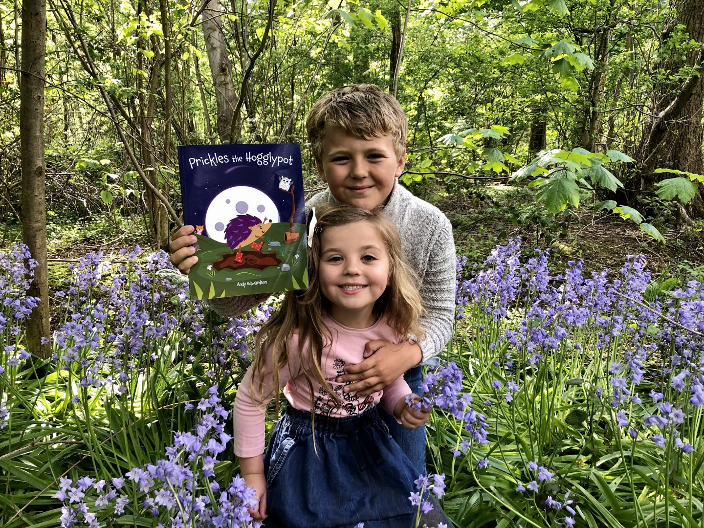 Harry holding a copy of Prickles the Hogglypot in the middle of a patch of bluebells